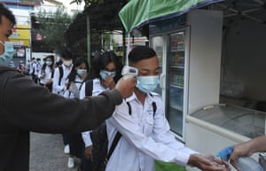 Students have their temperature checked and disinfect their hands to avoid the contact of coronavirus before their morning classes at Preah Sisowath high school, in Phnom Penh. Cambodia on Monday reopened schools after the country banned all state-organised events in the capital and a neighbouring province for two weeks after a number of people connected to a Hungarian official's visit tested positive in early November.