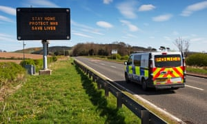 A police van drives past a road sign saying: 'Stay home, protect the NHS, save lives' neer Dundee.