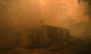 Firefighters work to protect a property in Kulnura as the Three Mile fire approaches Mangrove Mountain in NSW on Friday.