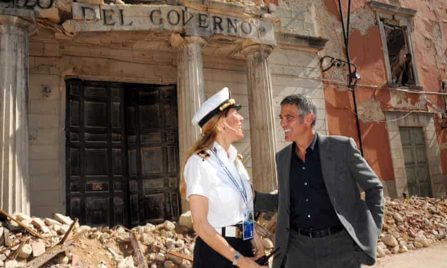 George Clooney chats to a police officer in l'Aquila before visiting San Demetrio ne' Vestini.