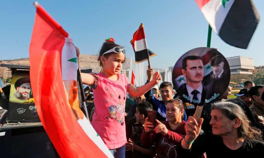 Syrians waving national flags and portraits of Bashar al-Assad at Umayyad Square.