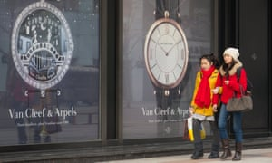 Chinese shoppers walk past windows advertising luxury watches in Beijing
