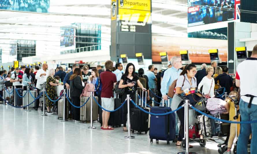 People queue inside terminal 5 at Heathrow airport.