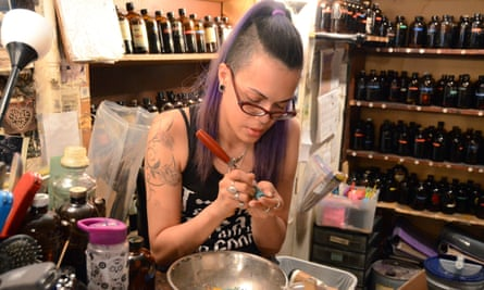 Enchantments occult shop in New York Carmen Pouerie carving candles.