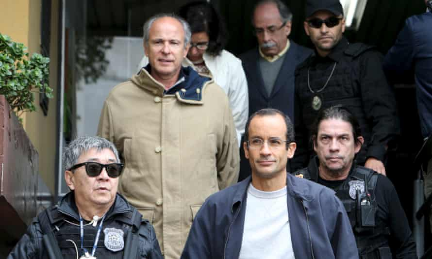Marcelo Odebrecht, bottom right, the head of engineering and construction company Odebrecht SA, and Otávio Marques Azevedo, second left, CEO of Brazil's second largest builder Andrade Gutierrez, are escorted by federal police officers in Curitiba on 20 June 2015.