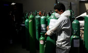 A volunteer carries an empty oxygen cylinder in Manus, Brazil