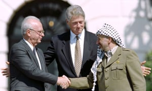 The Israeli prime minister Yitzahk Rabin and PLO leader Yasser Arafat shake hands for the first time (watched by Bill Clinton) after signing the historic Oslo peace accords in 1993.