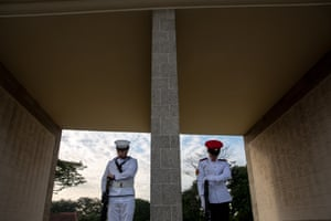 A British navy crewman (L) from HMS Argyll, and a Singapore armed forces honour guard (R) bow their heads during a commemoration ceremony at the Kranji War memorial