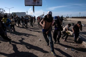 Central American migrants, mostly Hondurans, run along the Tijuana River near the El Chaparral border crossing in Tijuana, Mexico.