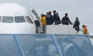 Migrants boarding an aeroplane.