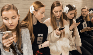 Models backstage at a fashion show, staring at their phones