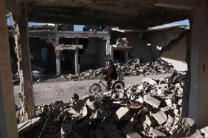 A man cycles past destroyed buildings in the rebel-held town on the outskirts of Damascus