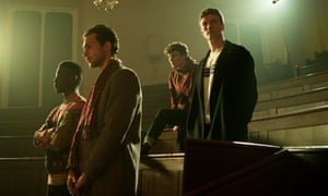 A still from the new series of Clique, showing male students Aubrey (Jyuddah Jaymes), Barney (Barney Haris), Calum (Nicholas Nunn) and Jack (Leo Suter) standing in a dimly-lit lecture theatre