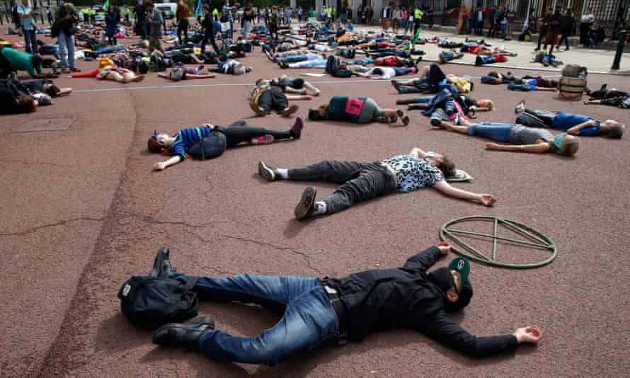 Extinction Rebellion protesters pretend to be dead outside Buckingham Palace on Saturday.