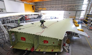 An employee inspecting an Airbus A380 wing at the manufacturer's Broughton plant