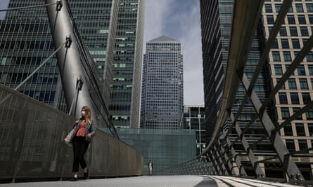 A woman crosses a bridge in front of One Canada Square in Canary Wharf