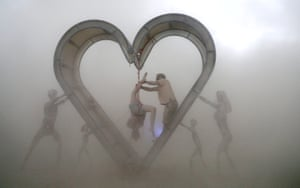 Participants perform a shibari rope scene during a desert duststorm at the Burning Man festival in the Black Rock desert of Nevada
