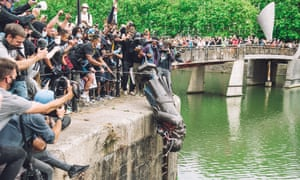 The statue of Colston is pushed into the river Avon, in front of cheering protesters.
