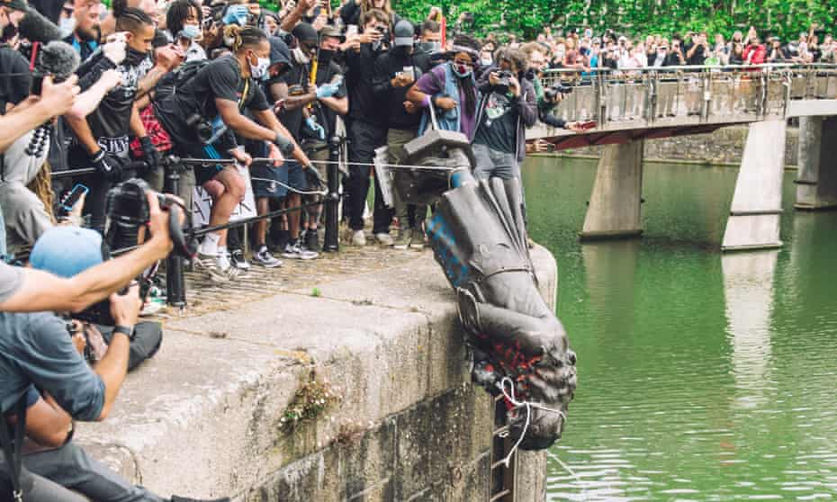 Black Lives Matter protesters push the statue of Edward Colston into Bristol Harbour.
