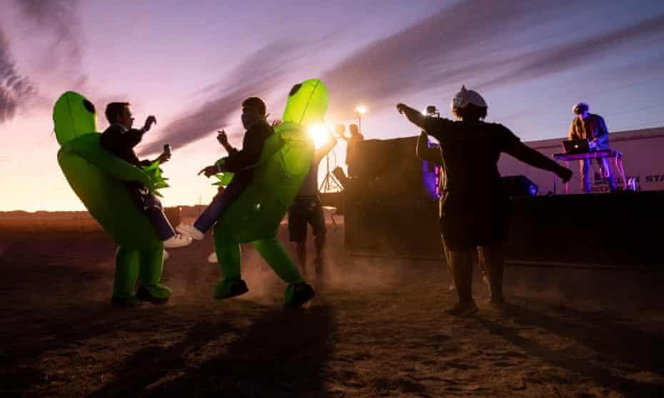 People in costume dance during a DJ set at 'Alienstock' in Rachel, Nevada.