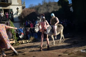 A reveller carries a chainsaw alongside a villager riding a donkey during carnival celebrations in Ituren