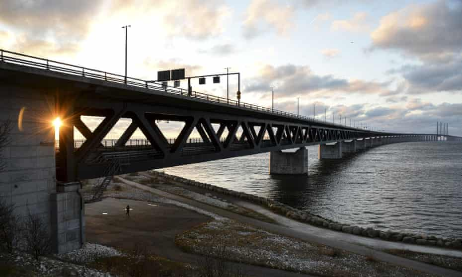 The sun sets over the Oresund Bridge between Sweden and Denmark as national border controls are re-introduced in both countries.