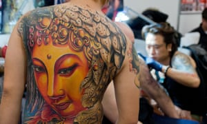 A huge Buddha head decorates a young man's back
