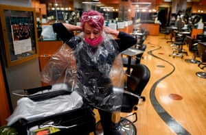A hairdresser tries a new safety barrier for clients before reopening in Virginia, US