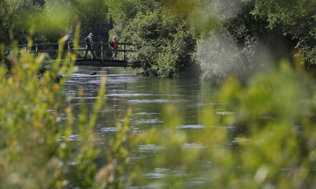 People cross a bridge over the River Itchen in Hampshire