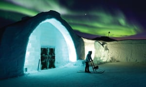 The Northern lights glowing behind the ice hotel