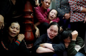 Relatives of John Hoang Van Tiep, one of the people who were found dead in the back of a British lorry last month, weep at his funeral