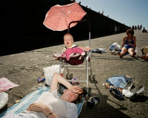 A baby cries beneath a parasol as a woman tries to get some rest