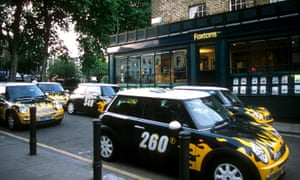 Green and yellow Foxtons-branded Minis parked outside one of its branches