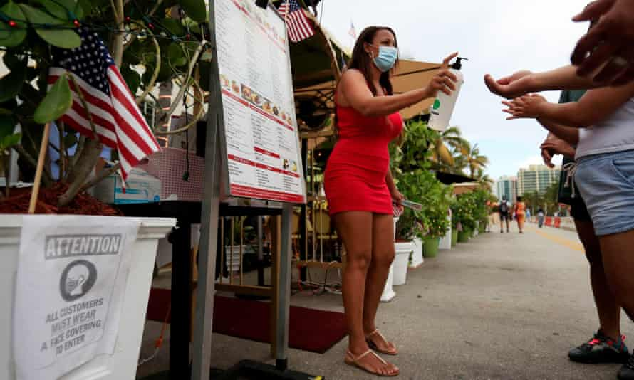 A hostess provides hand sanitizer to patrons entering a restaurant in Miami Beach, Florida, on 3 July.