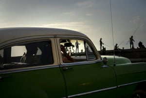 A couple in a classic American car drive along the Malecon seawall where fishermen work at sunset in Havana.