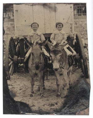 A ferrotype of two small boys on donkeys outside a bathing hut