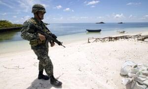 A Filipino soldier patrols the shore of Pagasa island