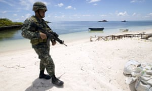 A Filipino soldier patrolling the shore of Pagasa island (Thitu Island) in the Spratly group of islands in the South China Sea.