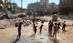Children play with water from a burst waterpipe at a site hit yesterday by an airstrike in Aleppo's rebel-controlled al-Mashad neighbourhood