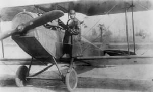 Photo of Bessie Coleman standing on the wing of her plane.