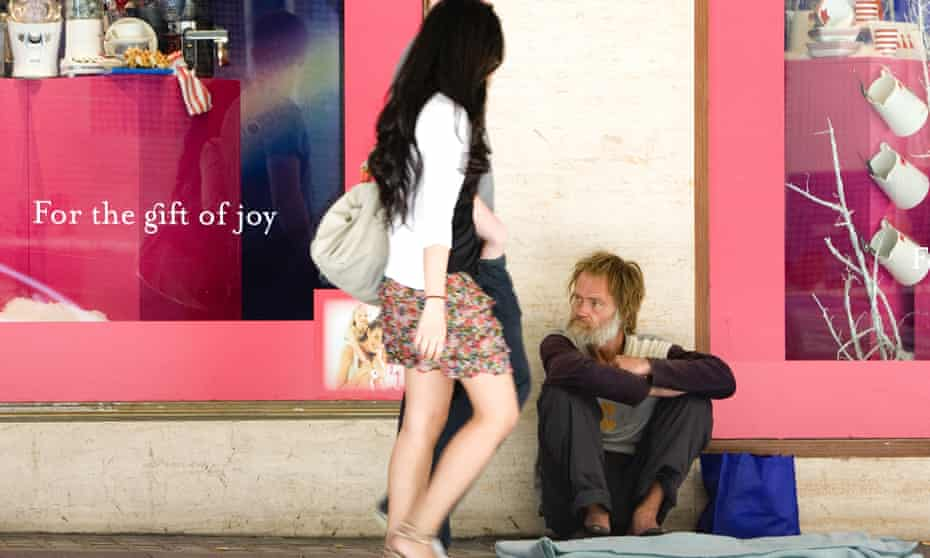 A man sits outside a department store in Sydney.