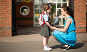 An attractive, smiling, happy young mum comforting &amp; picking up or dropping off her daughter at the infant school gates<br>E89BXJ An attractive, smiling, happy young mum comforting &amp; picking up or dropping off her daughter at the infant school gates