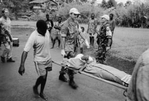 Peacekeeping troops from Australia and New Zealand carry a man who has been shot to a helicopter in Bougainville in 2000.