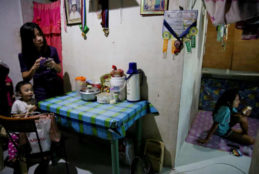 Janice Sarad watches television as her sister eats a snack at their home in Antipolo City, Rizal province