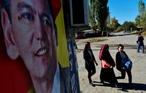Women walk past an election campaign poster of Kyrgyz opposition presidential candidate Omurbek Babanov in the outskirts of Bishkek.