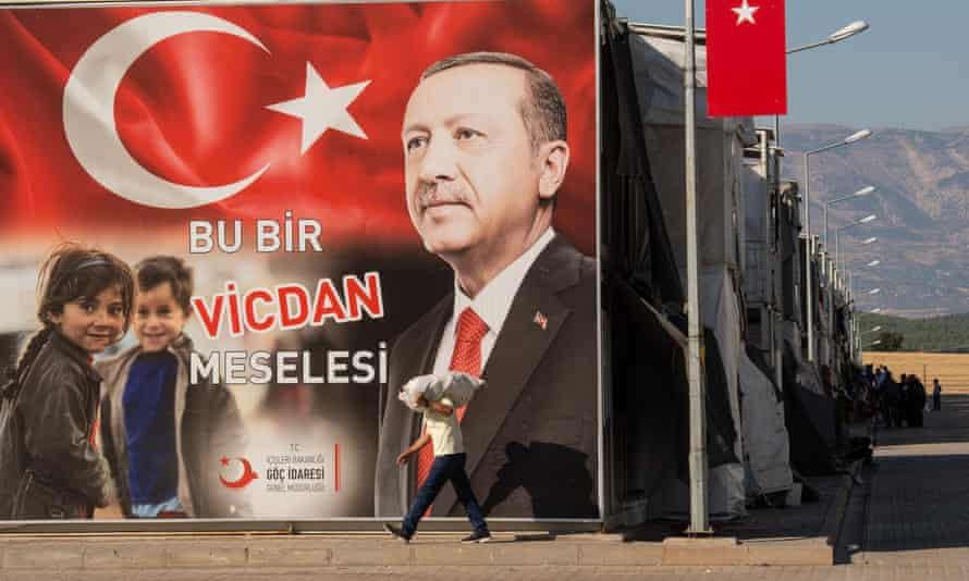A Syrian refugee walks past a poster of President Recep Tayyip Erdoğan that reads: 'It's a matter of conscience'