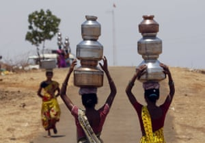 Indian women walk home after collecting drinking water from a well at Mengal Pada, in Maharashtra state