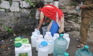 An Indian woman fills buckets in Shimla