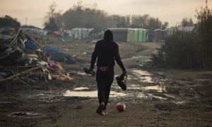 A man walks past destroyed tents in the camp.
