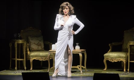 Joan Collins in a long white bias-cut dress on stage at the end of her show 'Joan Collins - Unscripted' at the London Palladium in 2016.